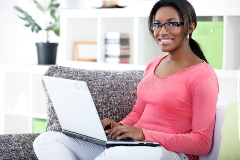Femme africaine à l'aide de l'ordinateur portable photographie stock libre de droits