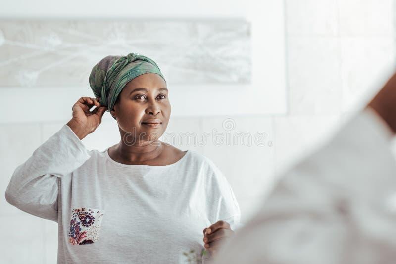 Femme africaine élégante mettant sur un foulard dans le miroir photographie stock
