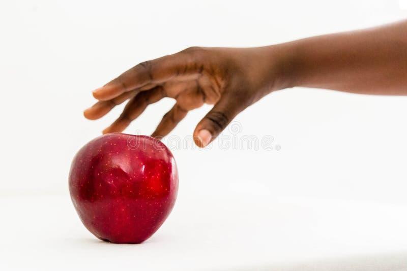 Femme africaine atteignant pour la pomme rouge Delicious dans la paume ouverte d'isolement sur un fond blanc photos stock