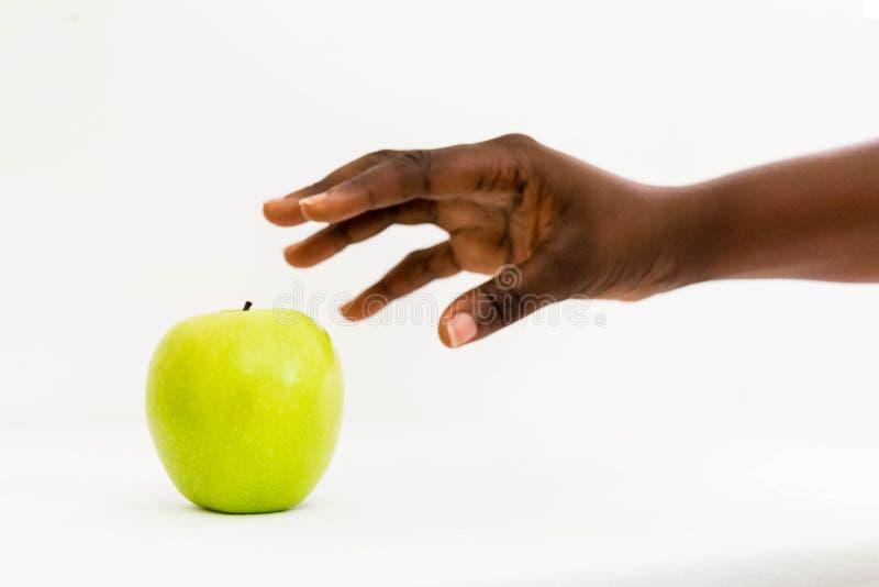 Femme africaine atteignant pour la pomme verte Delicious dans la paume ouverte d'isolement sur un fond blanc images libres de droits
