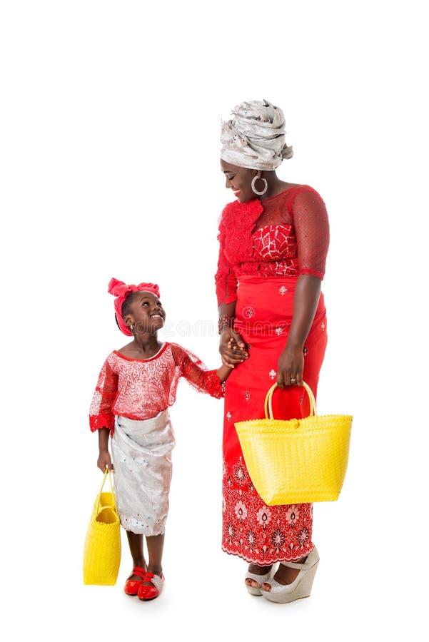 Femme africaine avec la petite fille dans l'habillement traditionnel avec le doigt photos libres de droits