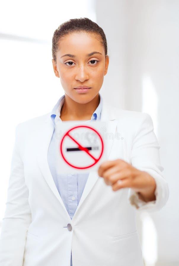 Femme africaine avec le signe non-fumeurs de restriction photographie stock libre de droits
