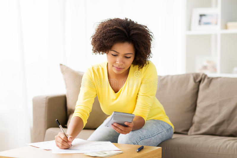 Femme africaine avec les papiers et la calculatrice à la maison photographie stock libre de droits
