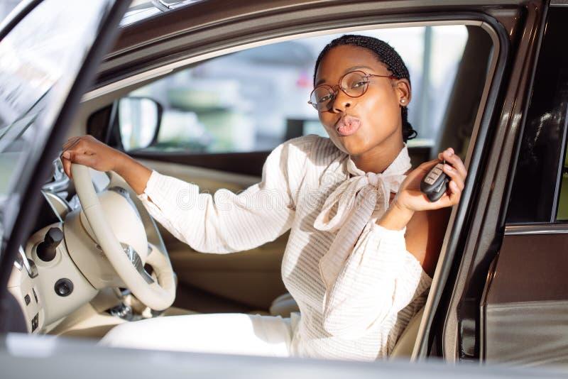 Femme africaine avec sa nouvelle voiture montrant la clé photo stock