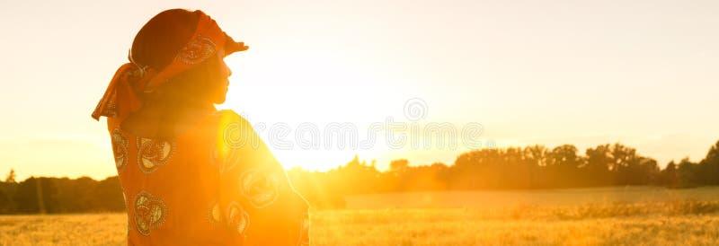Femme africaine dans des vêtements traditionnels se tenant dans un domaine des cultures au coucher du soleil ou au lever de solei photo stock