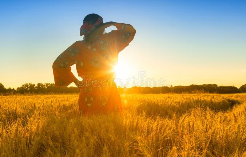 Femme africaine dans des vêtements traditionnels se tenant dans un domaine des cultures au coucher du soleil ou au lever de solei image stock