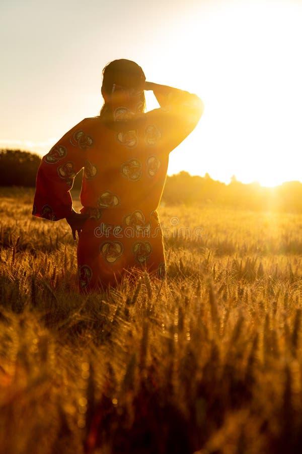 Femme africaine dans des v?tements traditionnels se tenant dans un domaine des cultures au coucher du soleil ou au lever de solei image libre de droits