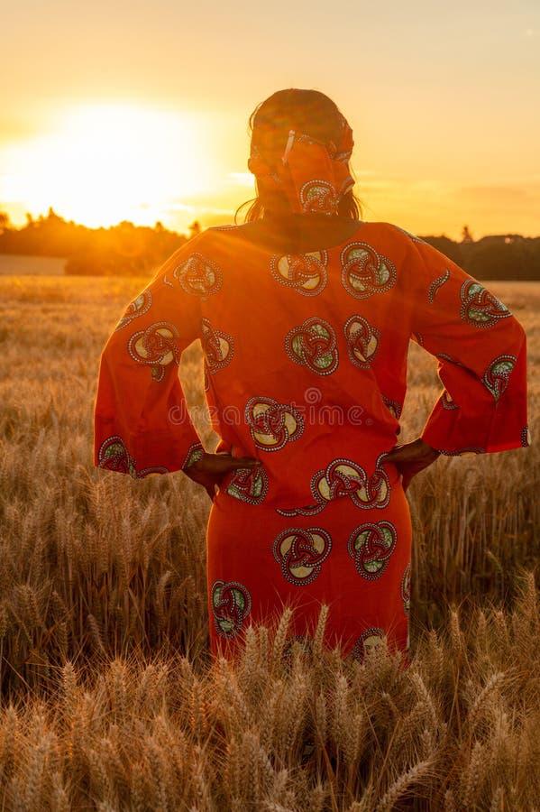 Femme africaine dans des v?tements traditionnels se tenant dans un domaine des cultures au coucher du soleil ou au lever de solei photo libre de droits