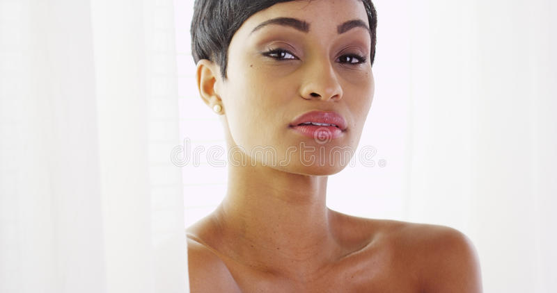 Femme africaine de beau torse nu regardant l'appareil-photo et jouant avec des rideaux photos libres de droits