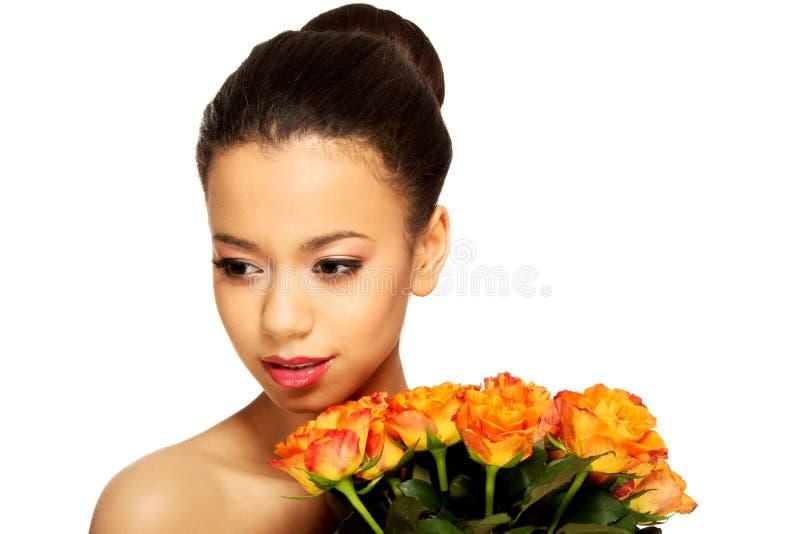 Femme africaine de beauté avec des roses photographie stock