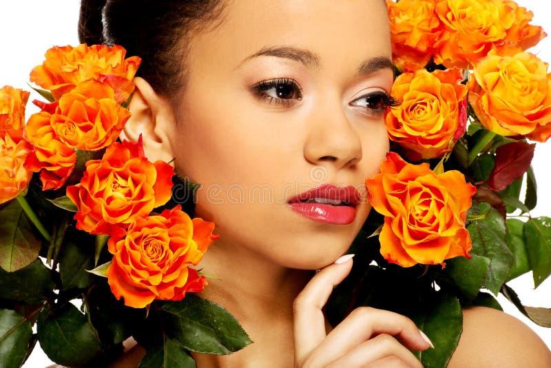 Femme africaine de beauté avec des roses image stock