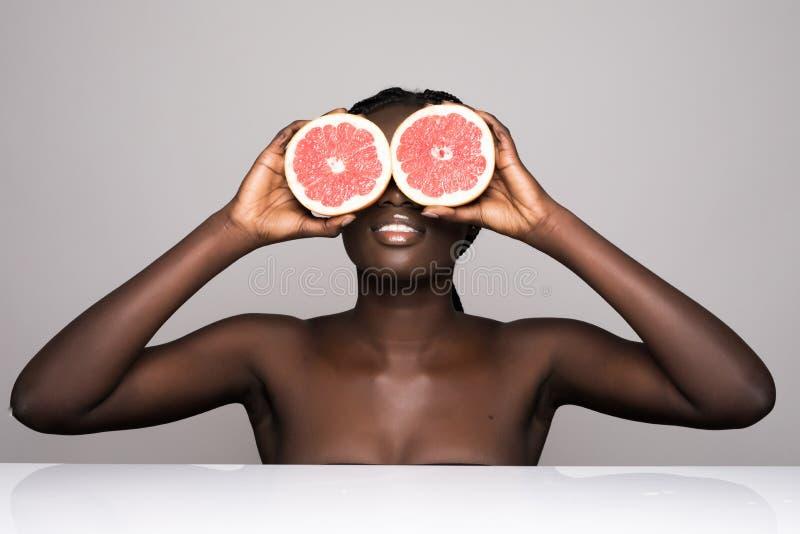 Femme africaine de beauté avec les yeux oranges de couverture de pamplemousse d'agrume avec le corps sain de peau Vitamine fraîch photos libres de droits