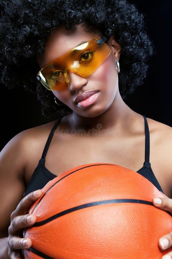 Femme africaine de fantaisie avec le basket-ball photographie stock