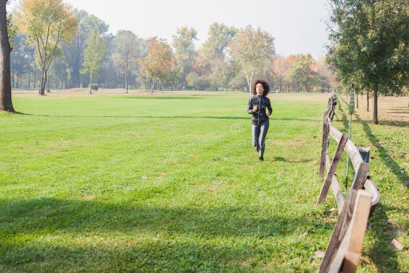 Femme africaine de forme physique pulsant aux champs verts en nature image libre de droits
