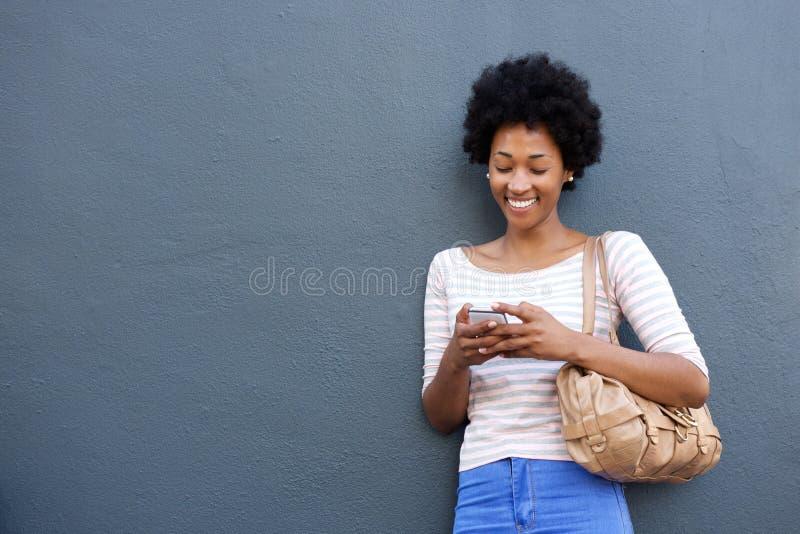 Femme africaine de sourire avec le sac regardant le téléphone portable images libres de droits