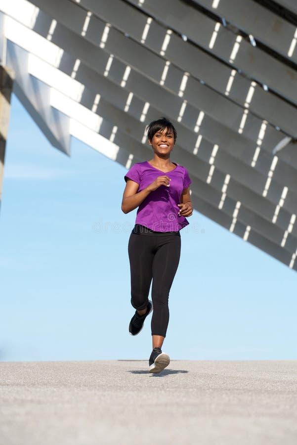 Femme africaine en bonne santé de plein corps jeune courant dehors image stock