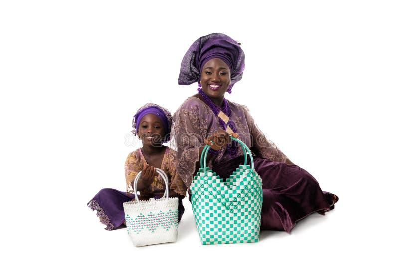 Femme africaine et petite fille dans l'habillement traditionnel avec des sacs d'emballage D'isolement photo libre de droits