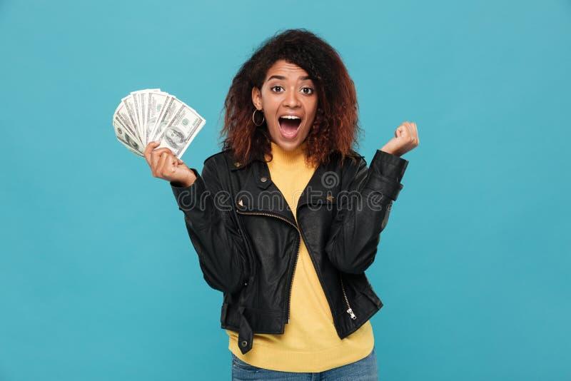 Femme africaine heureuse étonnée dans la veste en cuir tenant l'argent image stock