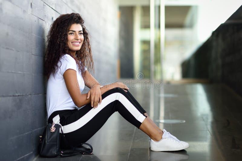 Femme africaine heureuse avec la coiffure bouclée noire se reposant sur le plancher urbain photo libre de droits