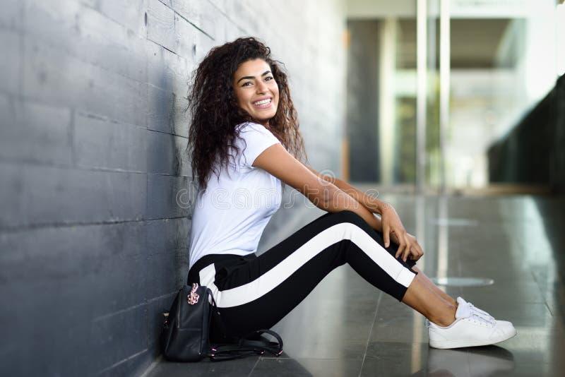 Femme africaine heureuse avec la coiffure boucl?e noire se reposant sur le plancher urbain images stock