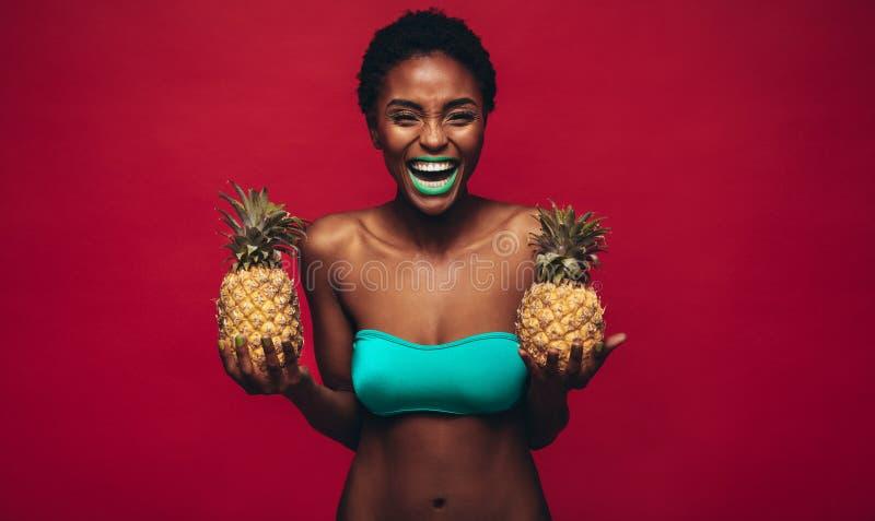 Femme africaine heureuse tenant les ananas frais images stock