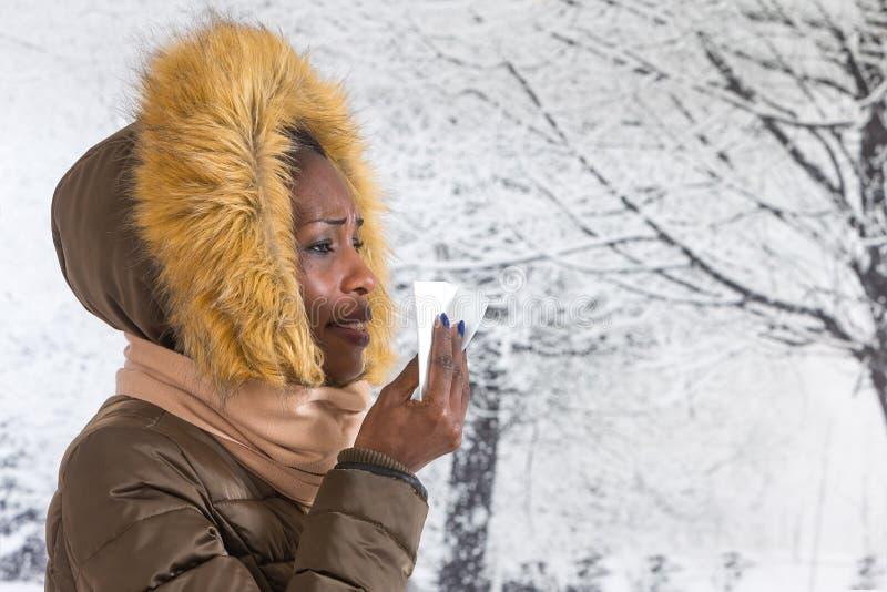Femme africaine malade de portrait de plan rapproché jeune avec le manteau à capuchon avec la fourrure, fond d'hiver de nez de so images libres de droits