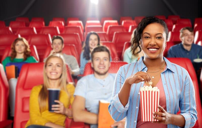 Femme africaine mangeant du maïs éclaté à la salle de cinéma photos stock