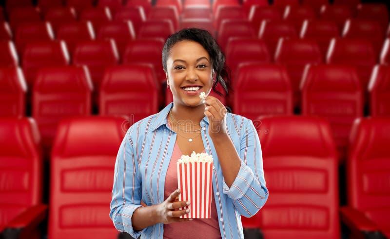 Femme africaine mangeant du ma?s ?clat? ? la salle de cin?ma image libre de droits