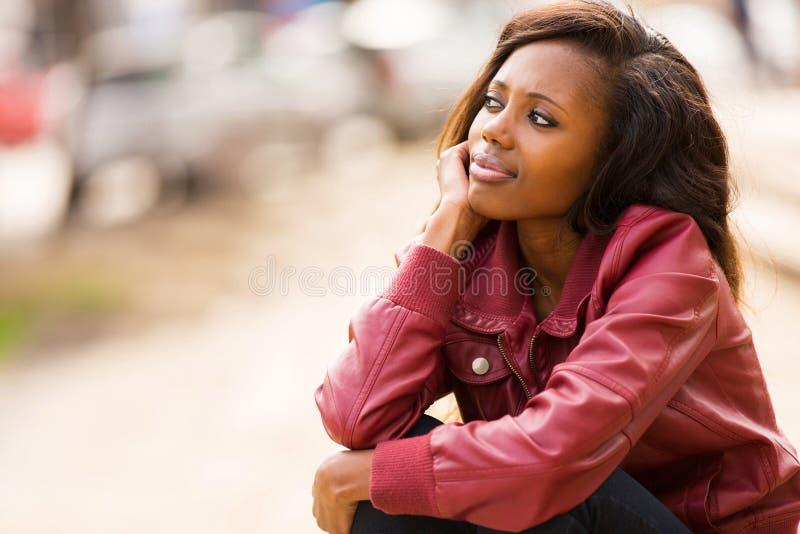 Femme africaine rêvassant image stock