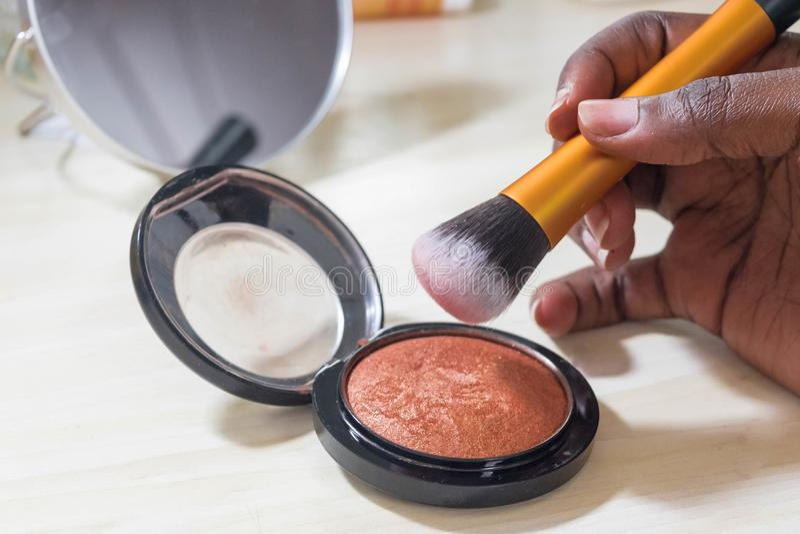 Femme africaine tenant la brosse de maquillage au-dessus de la barre de mise en valeur de bronzer images libres de droits
