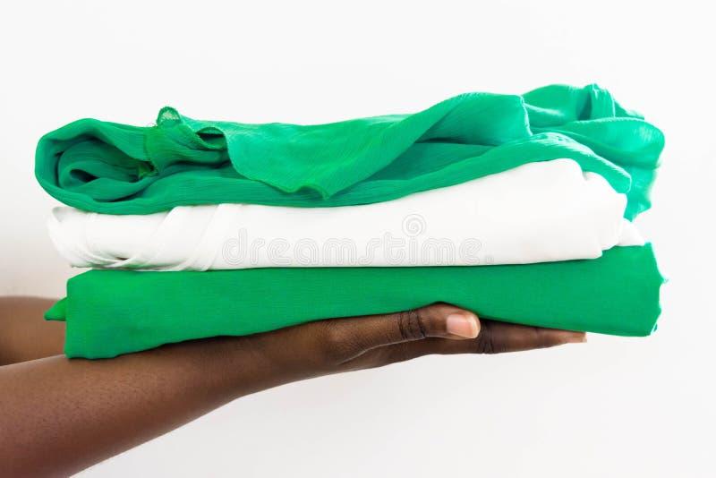Femme africaine tenant une pile d'habillement dans des deux mains photos libres de droits