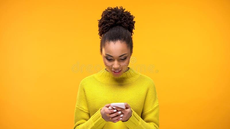 Femme afro-américaine à l'aide du smartphone, application de encaisser en ligne, dispositif image stock