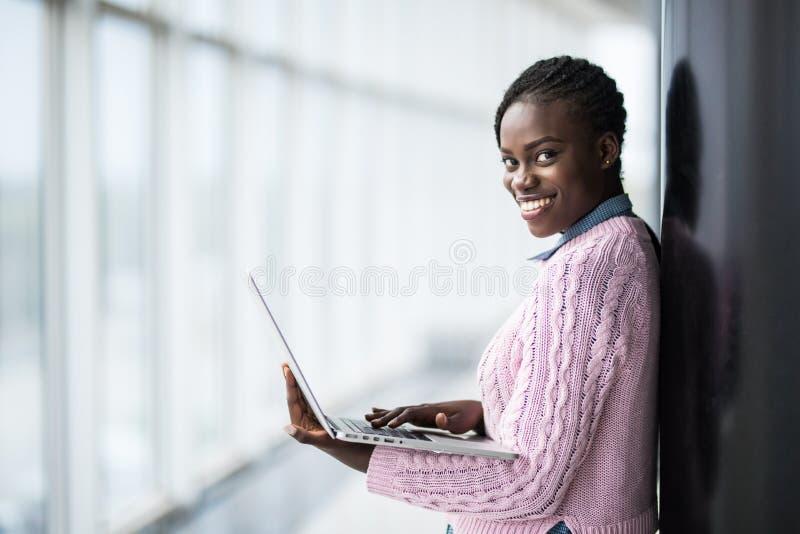 Femme afro-américaine d'étudiant de jeune beauté tenant l'ordinateur portable ouvert sur le fond d'université panoramique de fenê photos stock