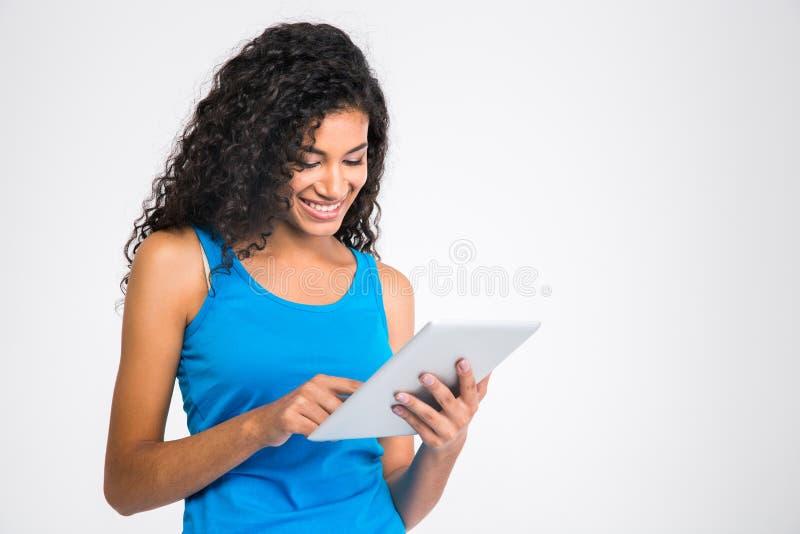 Femme afro-américaine de sourire à l'aide de la tablette images libres de droits