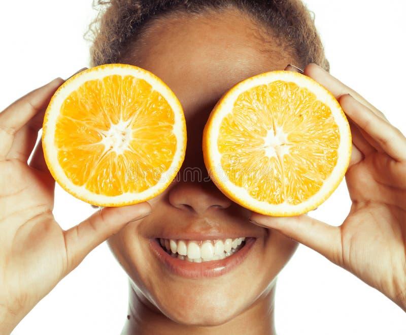 Femme afro-américaine de sourire de jeunes avec de demi oranges, concept de mode de vie d'isolement sur le fond blanc photos stock