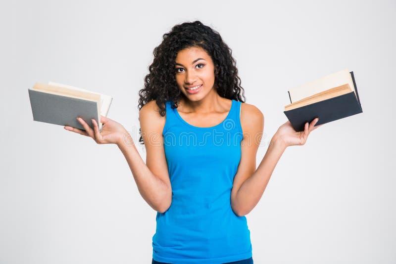 Femme afro-américaine de sourire tenant deux livres photos stock
