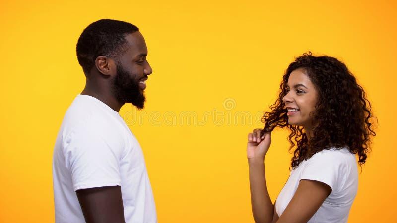 Femme afro-américaine espiègle flirtant avec l'homme de couleur, date romantique d'invitation photographie stock