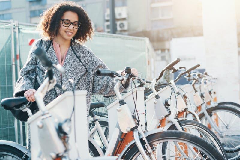 Femme afro-américaine prenant une bicyclette dans un vélo partageant la plate-forme image stock