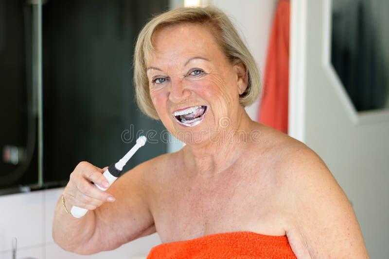 Femme agée à l'aide d'une brosse à dents électrique photographie stock libre de droits
