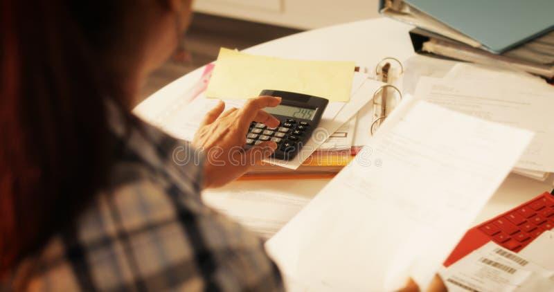 Femme agée à l'aide de la calculatrice pour les impôts et le budget à la maison images libres de droits