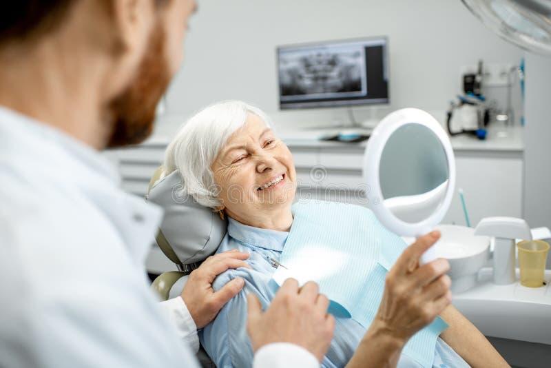 Femme agée appréciant son sourire dans le bureau dentaire image libre de droits