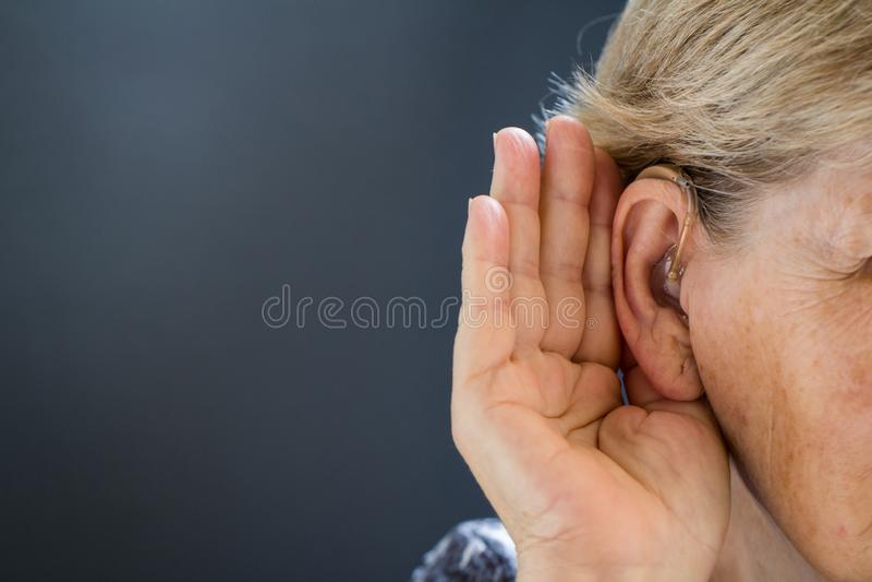 Femme agée avec la perte d'audition sur le fond gris Relatif à l'âge image stock