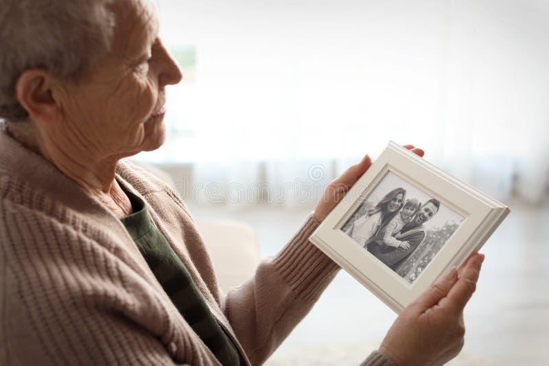 Femme agée avec le portrait encadré de famille images libres de droits