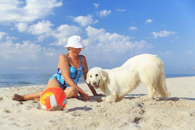 Femme agée avec son chien d'arrêt de golder sur une mer photo libre de droits