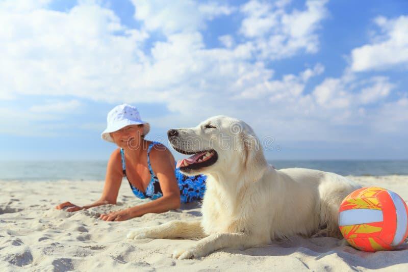 Femme agée avec son chien d'arrêt de golder sur une mer photos stock
