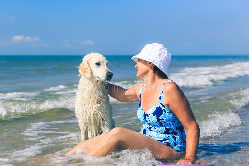 Femme agée avec son chien d'arrêt de golder sur une mer image libre de droits