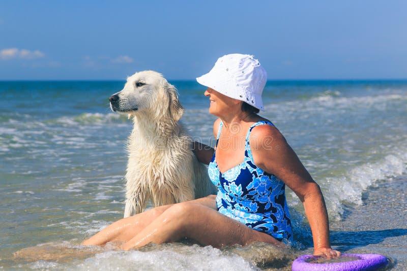 Femme agée avec son chien d'arrêt de golder sur une mer images stock
