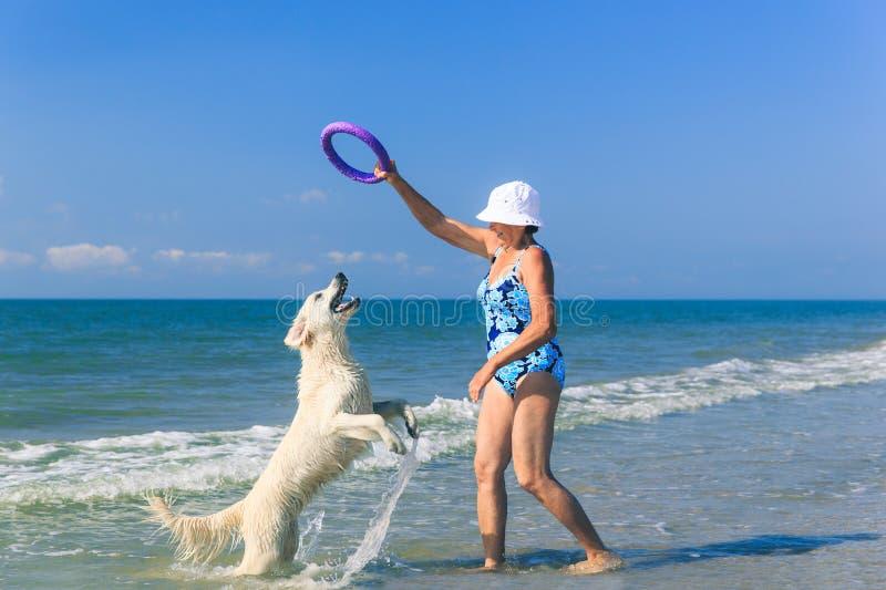 Femme agée avec son chien d'arrêt de golder sur une mer photographie stock libre de droits