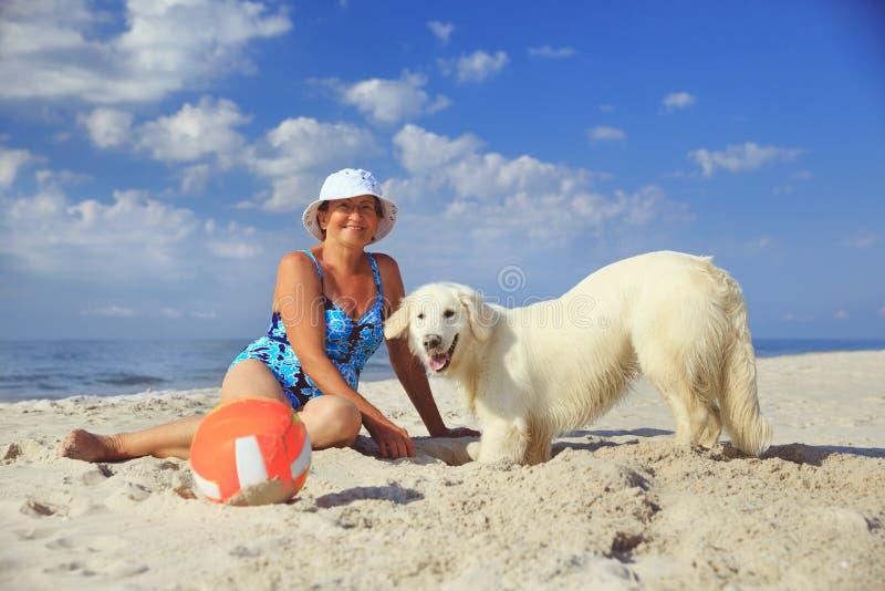 Femme agée avec son chien d'arrêt de golder sur une mer photos libres de droits