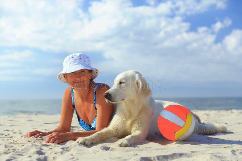 Femme agée avec son chien d'arrêt de golder sur une mer images libres de droits